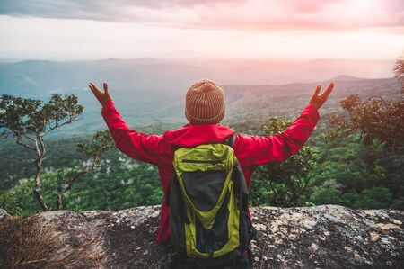 Hikers climbing a red rain jacket carrying a backpack Sitting on the edge of a cliff See the beauty of the mountains at sunset, showing success, freedom and adventure.