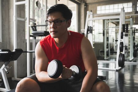 Strong muscular asian man workout in gym doing exercises at biceps. Weight training concept.