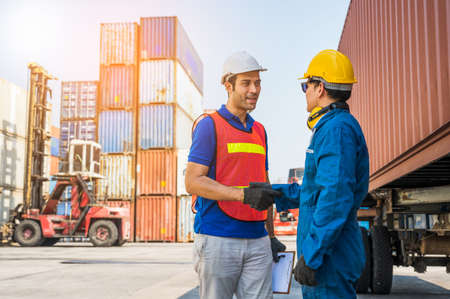 Foreman and dock worker staff shaking hand for sucess working at Container cargo harbor. Business Logistics import export shipping concept.