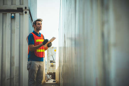 Foreman holding clipboard working at Container cargo harbor. Business Logistics import export shipping concept. Banco de Imagens