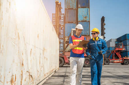 Foreman and dock worker staff working checking at Container cargo harbor holding clipboard. Business Logistics import export shipping concept. Stock Photo
