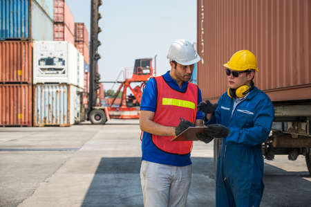 Foreman and dock worker staff working checking at Container cargo harbor holding clipboard. Business Logistics import export shipping concept.