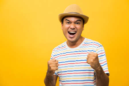 Happy young asian man celebrates with two hand in the air on yellow background.