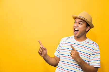 Young happy&funny asian man pointing finger on blank space for text on yellow background.