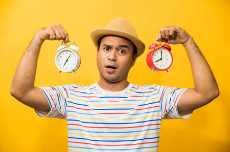 Young asian man holding the alarm clock on yellow isolated background. Stock Photo