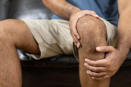 Men have rheumatoid arthritis. He has a knee pain. With both hands to hold the knee Stock Photo