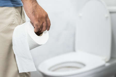 One man has diarrhea He then went to the bathroom to take numbers two. In his hand he had tissue paper to wash and clean.