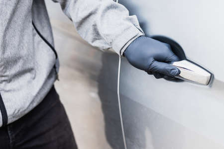 The thief pull up the door handle to Stealing a car. The vehicle insurance concept.