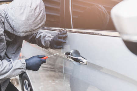 The thief uses a screwdriver Stealing a car at the door handle. The vehicle insurance concept.