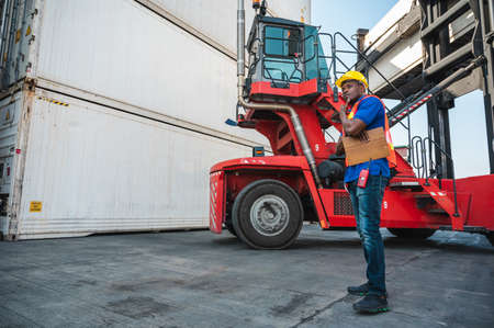 Black foreman worker working control the crane and forklift at Container cargo harbor to loading containers. African dock male staff for Logistics import export shipping concept.