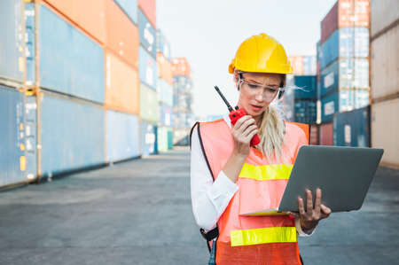 Foreman woman worker working checking at Container cargo harbor holding laptop computer and radio walkie-talkie to loading containers. Dock female staff business Logistics import export shipping concept. Imagens