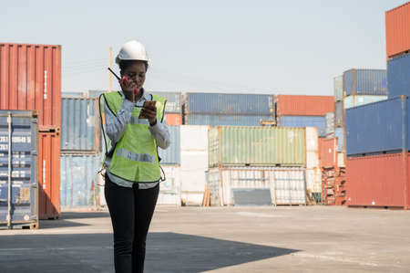 Black foreman woman worker working checking at Container cargo harbor holding radio walkie-talkie and smartphone to loading containers. African dock female staff business Logistics import export shipping concept.