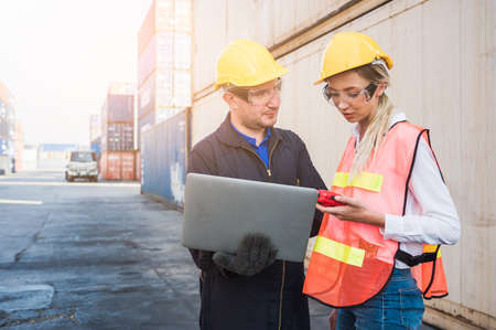 Two foreman man & woman worker working checking at Container cargo harbor holding laptop computer and using walkie-talkie to loading containers. Dock male and female staff business Logistics import export shipping concept.