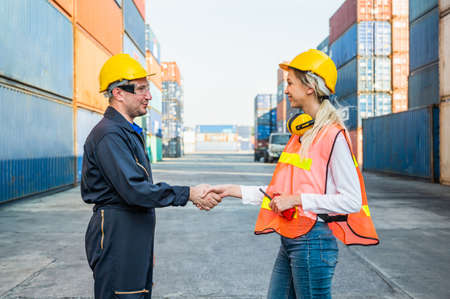 Happy dealing shaking hands two foreman man & woman worker working checking at Container cargo harbor to loading containers. Dock male and female staff business Logistics import export shipping concept. Imagens