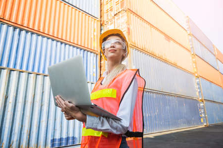 Foreman woman worker working checking at Container cargo harbor holding laptop computer to loading containers. Dock female staff business Logistics import export shipping concept.
