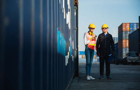 Two foreman man & woman worker working checking at Container cargo harbor to loading containers. Dock male and female staff business Logistics import export shipping concept.