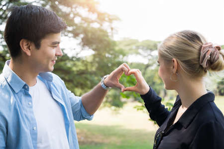 Young couple lovers doing love sign in the park Romanticly. On a relaxing holiday.