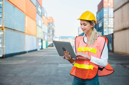 Foreman woman worker working checking at Container cargo harbor holding laptop computer to loading containers. Dock female staff business Logistics import export shipping concept. Banco de Imagens