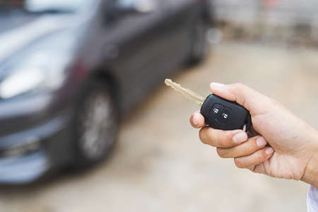 Hand presses on the remote control to lock car. Stock Photo