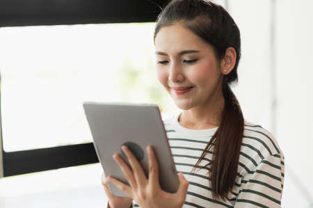 Asian woman using tablet. Smiling pretty woman sitting and work from home.
