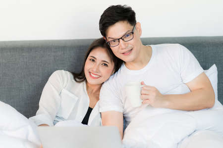 Young asian couple love man and woman watching movie in laptop on the bed in the morning. Happy moment concept.