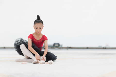 Asian ballerina girl tying pointe shoelace before practicing the ballet dancing sitting on rooftop of the building top view of urban city background.