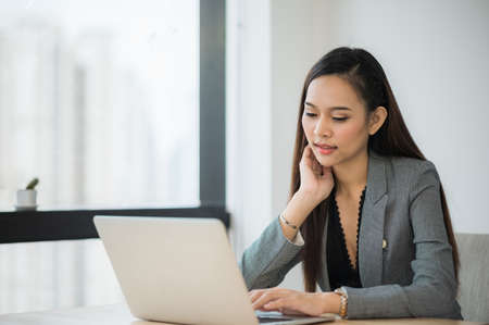 Beautiful asian businesswoman using laptop working in office and smiling.