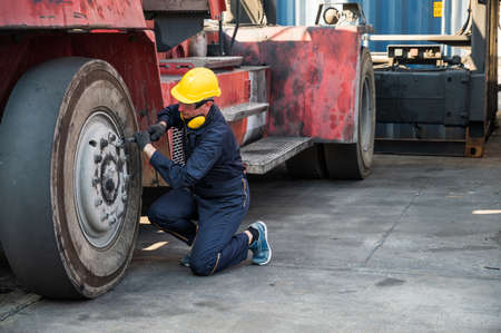 Worker man operate checking and fix the wheels forklift crane at container cargo harbor.