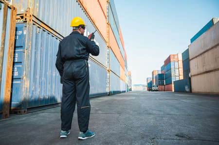 Foreman worker working checking at Container cargo harbor holding radio walkie-talkie to loading containers. Dock male staff business Logistics import export shipping concept. Stock fotó
