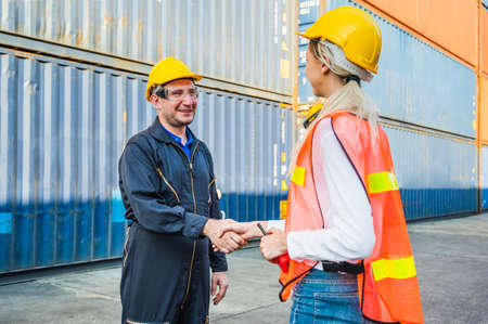 Happy dealing shaking hands two foreman man & woman worker working checking at Container cargo harbor to loading containers. Dock male and female staff business Logistics import export shipping concept. Stock fotó