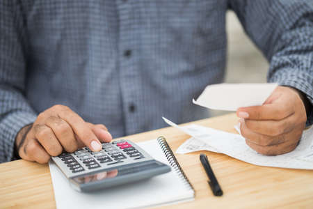 Businessman using calculator and calculate bills of payment per month. Financial buying payment income expenditure.