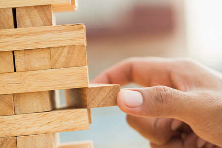 Close up male hand holding arranging or pick up the block wood game and stacking. Growth of Business financial investment and bankrupt concept.