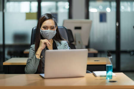 Young asian businesswoman using laptop sitting in modern office working with social distancing wearing mask alcohol gel on desk.