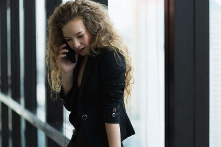 Beautiful sexy woman talking on smartphone standing near window in office.