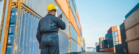 Foreman worker working checking at Container cargo harbor holding radio walkie-talkie to loading containers. Dock male staff business Logistics import export shipping concept. Reklamní fotografie