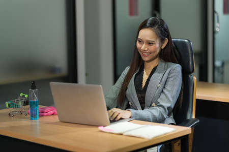 Young asian businesswoman using laptop sitting in modern office working with social distancing alcohol gel on desk.