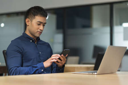 Young asian businessman using smartphone while working in office. Reklamní fotografie