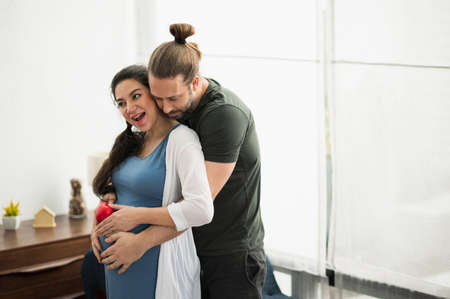 Handsome beard man take care his pregnant wife. Happy family concept. Reklamní fotografie