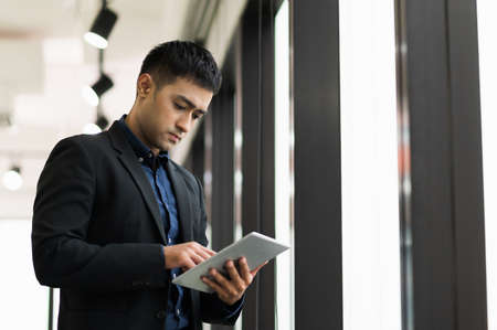 Young handsome asian businessman in suit standing near window using tablet in office.