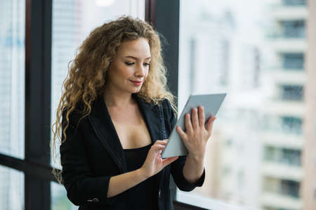 Young beautiful business woman standing near window using tablet in office. Smiling sexy lady confident in black suited.
