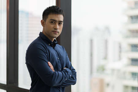 Young handsome asian businessman standing near window with arm crossed in office.