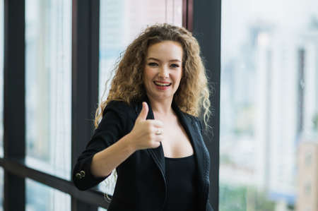 Young beautiful business woman standing near window in office. Smiling sexy lady confident in black suited showing thumbs up.