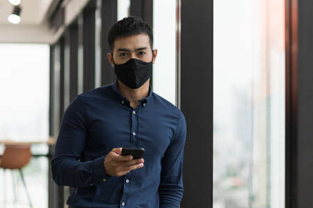 Business asian man wearing protection face mask holding smartphone work in office. Reklamní fotografie