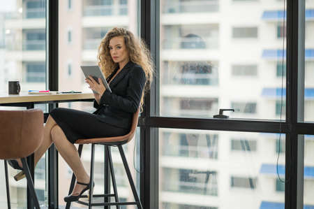 Young beautiful business woman near window using tablet in office. Smiling sexy lady confident in black suited.