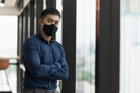Business asian man wearing protection face mask standing near window in office.