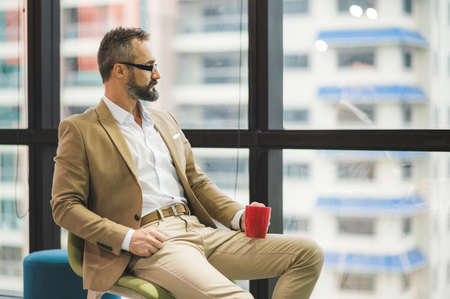 Young handsome business bearded man drinking cup of coffee sitting near window in office work place.