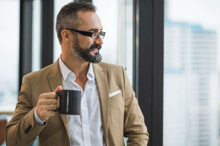 Young handsome business bearded man drinking cup of coffee standing near window and look outside in office work place.