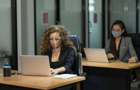 Business people working with laptop in office wearing protection face mask.
