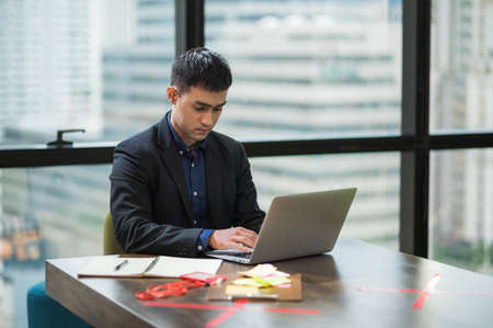 Young asian businessman working with laptop in office.