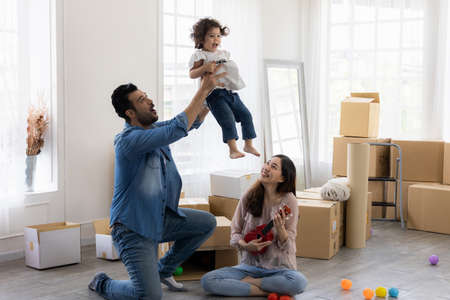 Father raise the daughter up. They play ukulele sitting on the floor in the living room and listen to the music. The family just moved to a new house. Happy moment Multi-ethnic dad mom and child.